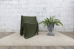 Front view of green cloth cover the wooden chair with cement wall and vase stock image