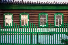 Front view on green log cabin facade in the winter. Royalty Free Stock Photo
