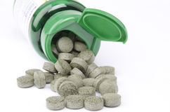 Front view of a green vitamin bottle and pills Stock Image