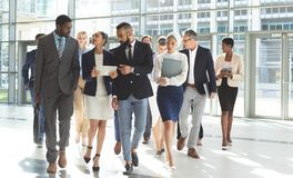 Front view of group of diverse business people walking together in lobby office royalty free stock photos