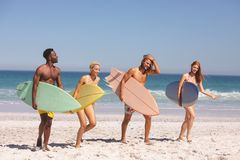 Group of friends walking with surfboard on the beach. Front view of group of diverse friends walking with surfboard on the beach royalty free stock photography