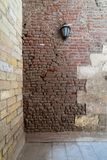 Front view of grunge weathered two perpendicular uneven stone bricks wall with one lantern. Medieval Cairo, Egypt royalty free stock images