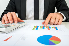 Front view of the hands of a accountant analysing a bar graph Royalty Free Stock Image