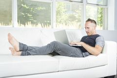 Front view of a handsome man using  laptop sitting on couch at home Royalty Free Stock Photos