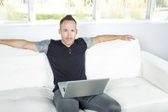 Front view of a handsome man using  laptop sitting on couch at home Royalty Free Stock Image