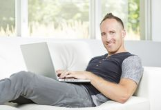 Front view of a handsome man using  laptop sitting on couch at home Stock Images