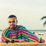 Front view of handsome positive Mexican bartender standing on th. E bar counter and relaxing at the resort, toned image Royalty Free Stock Photography