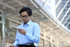 Front view of handsome young Asian business man in blue shirt looking mobile smart phone at outside office stock photos