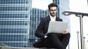 Front view of a handsome young businessman working with a laptop outside stock footage