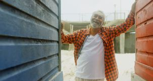Front view of happy active senior African American man standing at beach hut on a sunny day 4k. Front view of happy active senior African American man standing stock video footage