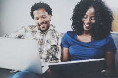 Front view of Happy african american couple relaxing together on the sofa.Young black man and his girlfriend using Royalty Free Stock Image