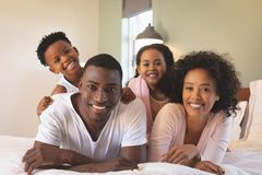 Happy African American family lying on bed and looking at camera stock images