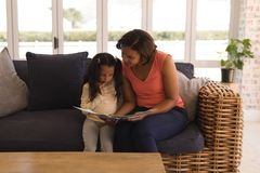 Grandmother and granddaughter reading a story book in living room stock photos