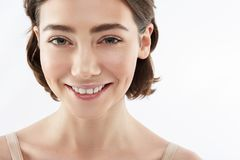 Front view of happy brunette female on white stock photography