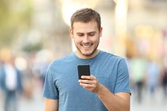 Front view of a guy checking a smart phone outside Royalty Free Stock Photos