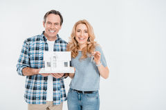 Front view of happy couple holding house model and keys Royalty Free Stock Photos