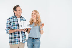 Front view of happy couple holding house model and keys Royalty Free Stock Photo