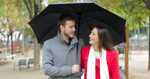Couple walking and talking under the rain stock video footage
