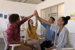 Business colleagues giving high five to each other in office. Front view of happy diverse business colleagues giving high five to each other after successful royalty free stock image