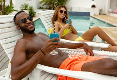 Couple having cocktail drink while relaxing on a sun lounger. Front view of happy diverse couple having cocktail drink while relaxing on a sun lounger near stock photography