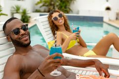 Couple having cocktail drink while relaxing on a sun lounger. Front view of happy diverse couple having cocktail drink while relaxing on a sun lounger near stock photos