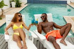Couple toasting glasses of cocktail while relaxing on a sun lounger near swimming pool. Front view of happy diverse couple toasting glasses of cocktail while stock images