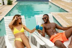 Couple toasting glasses of cocktail while relaxing on a sun lounger near swimming pool. Front view of happy diverse couple toasting glasses of cocktail while royalty free stock photos