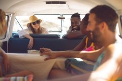 Group of friends having fun in a camper van at beach. Front view of happy group of diverse friends having fun in a camper van at beach royalty free stock photography