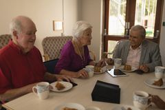 Front view of happy group of senior friends having breakfast on dining table royalty free stock photo