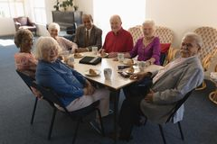 Front view of happy group of senior friends sitting on dining table and looking at camera royalty free stock photography