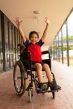 Happy disabled schoolboy with arms up looking at camera in corridor