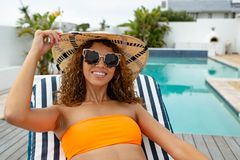 Woman in bikini relaxing on a sun lounger near swimming pool at the backyard of home. Front view of happy mixed-race woman in bikini relaxing on a sun lounger stock photo