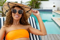 Woman in bikini relaxing on a sun lounger near swimming pool at the backyard of home. Front view of happy mixed-race woman in bikini relaxing on a sun lounger stock image