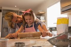 Mother with her daughter preparing food in kitchen. Front view of happy mother helping her daughter roll out cookie dough in kitchen at home royalty free stock photos