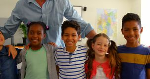 Front view of happy multi-ethnic schoolkids with Caucasian male schoolteacher standing in classroom stock video footage