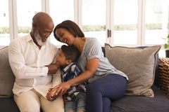 Multi-generation family sitting on sofa in living room. Front view of a happy multi-generation African American family sitting on sofa in living room at home stock image