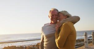 Senior couple embracing each other alongside beach