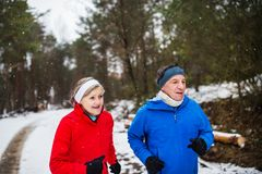 A front view of senior couple jogging in snowy winter nature. A front view of happy senior couple jogging in snowy winter nature royalty free stock images