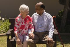 Front view of senior couple sitting on bench and looking each other in garden royalty free stock photography