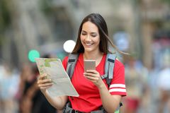 Teen tourist searching location online on the street. Front view of a happy teen tourist searching location online walking on the street royalty free stock photo