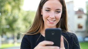Happy woman walks using a smart phone stock video footage