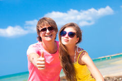 Front view of happy young couple on beach smiling Royalty Free Stock Image