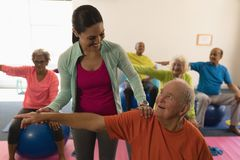 Young female trainer assisting senior man in fitness studio. Front view of happy young female trainer assisting senior man in fitness studio royalty free stock photos