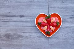 Front view of a heart-shaped dish with strawberries and tangerine inside, on a neutral gray floor stock image