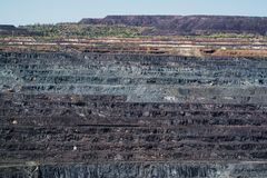 Huge open pit side. Layers of Earth. Front view of horizontal layers in a quarry at daytime royalty free stock images