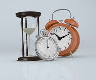 Time concept. Front view of an hourglass  with a analog clock and a stopwatch (3d render Stock Photo