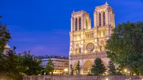Front view of Notre Dame De Paris cathedral day to night timelapse after sunset. Front view of illuminated Notre Dame De Paris cathedral day to night transition stock footage
