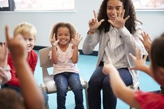 Front view of infant school children sitting on chairs in a circle in the classroom, holding up their hands and learning to count. With their female teacher stock photos
