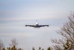 Airplane ist landing. Front view of a jet airplane approaching an airport for landing Royalty Free Stock Photo