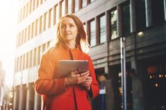 Front View Jonge aantrekkelijke vrouw in oranje laag die zich op de computer van de de holdingstablet van de stadsstraat bevinden Stock Foto